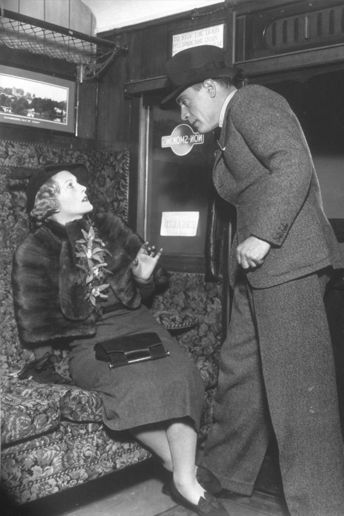 28th March 1936: A man confronts a woman in a train carriage, in a scene from the play 'Her Last Adventure', at the Ambassador's Theatre, London. (Photo by Sasha/Getty Images)