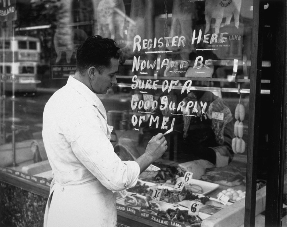 September 5th 1939: A butcher painting a meat registration notice on the window of his shop: 'Register Here Now And Be Sure Of A Good Supply Of Meat'. (Photo by Fox Photos/Getty Images)