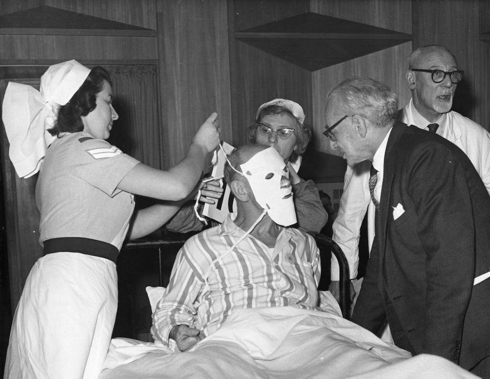 7th December 1964:  Parliamentary Secretary to the Ministry of Health Sir Barnett Stross talks to a patient with facial burns at the Fairfield Halls, Croydon. Nurses carry out dressing work for the National Finals of a competition for the Minister of Health's Cup held by the National Hospital Hospital Service Reserve.  (Photo by Harry Todd/Fox Photos/Getty Images)
