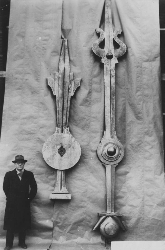 7th February 1950:  Hands of an enormous clock which is being built in Strasbourg for export to Oslo, Norway. M Ungerer the designer and craftsman stands by the hands which weigh over 500lbs.  (Photo by Keystone/Getty Images)
