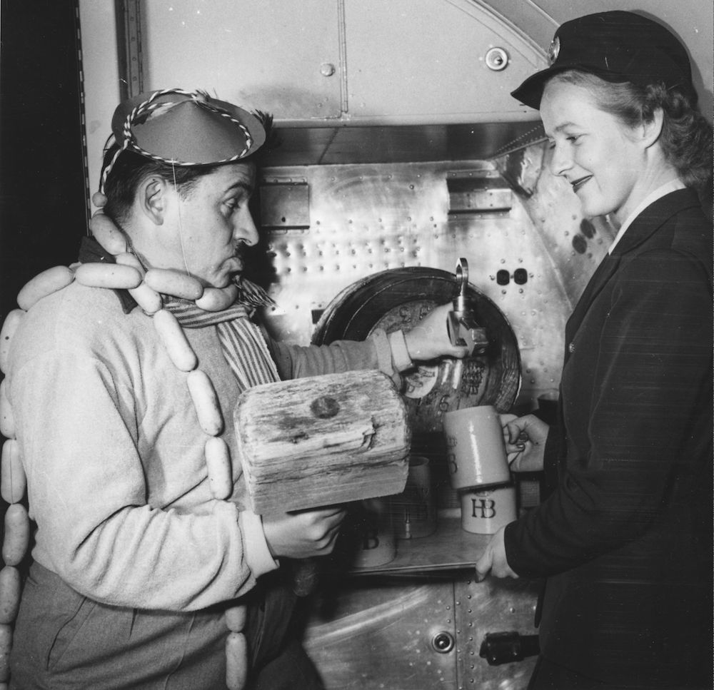 1952: Butcher Kurt Pratsch-Kaufmann and an air stewardess making catering preparations for a flight to Munich. Passengers are treated to a hot dog and glass of beer to promote Munich's October Festival. (Photo by Keystone/Getty Images)