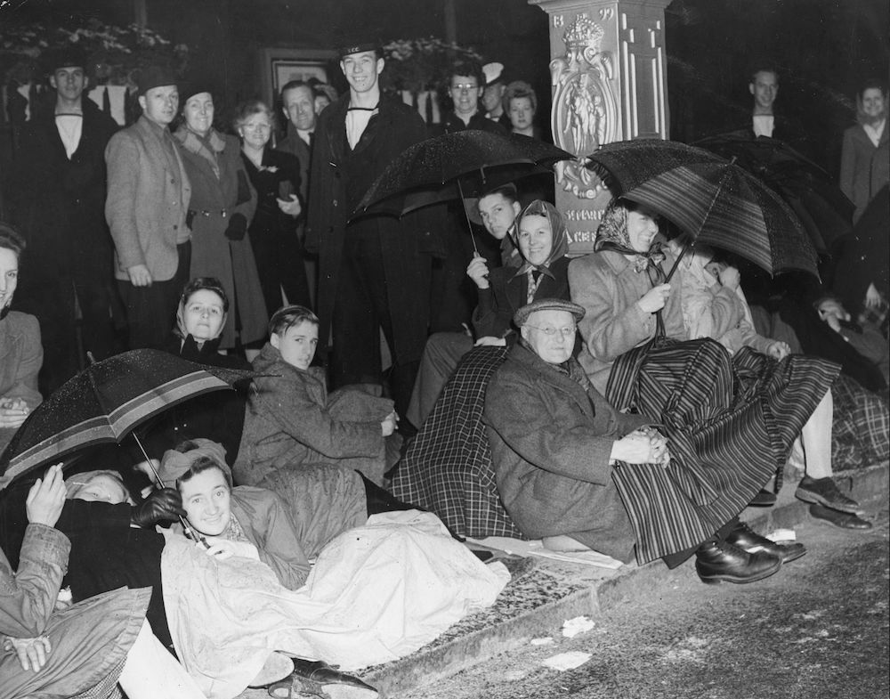 7th June 1946:  A crowd of people, some sheltering under umbrellas, by the roadside at Whitehall, London, in readiness for the Victory Parade.  (Photo by Keystone/Getty Images)