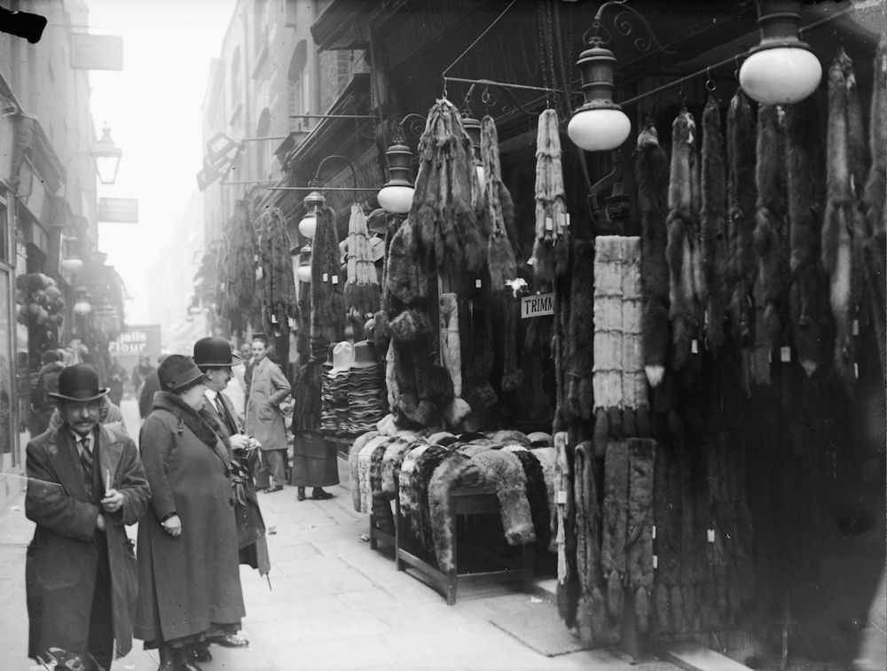 April 1929: Fur coats and accessories hang outside a fur stall in Berwick Street Market, London. (Photo by Fox Photos/Getty Images)