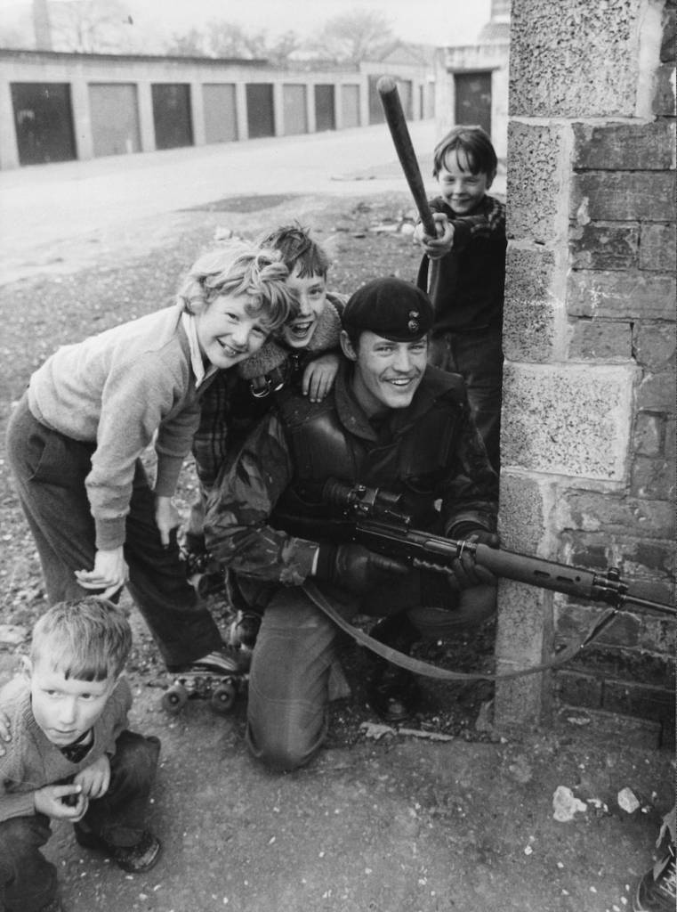 13th May 1981: Schoolboys in a Catholic area of Belfast at play on the streets near a British soldier on patrol. (Photo by Rob Taggart/Central Press/Getty Images)