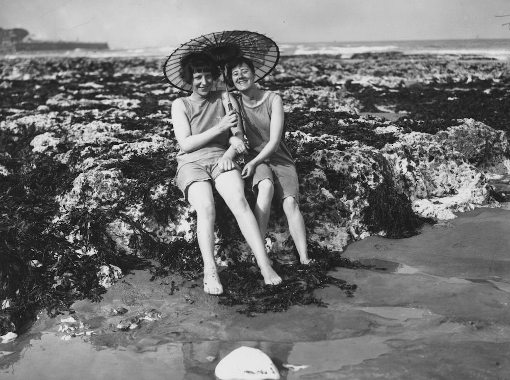 7th May 1928:  Two bathers sitting on the rocks at Broadstairs beach under a parasol.  (Photo by Davis/Topical Press Agency/Getty Images)