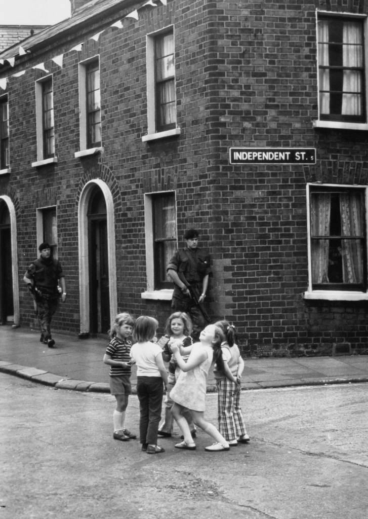 31st October 1974: Children play on the corner of Independent St in Belfast ignoring the armed soldiers on patrol. (Photo by Keystone/Getty Images)