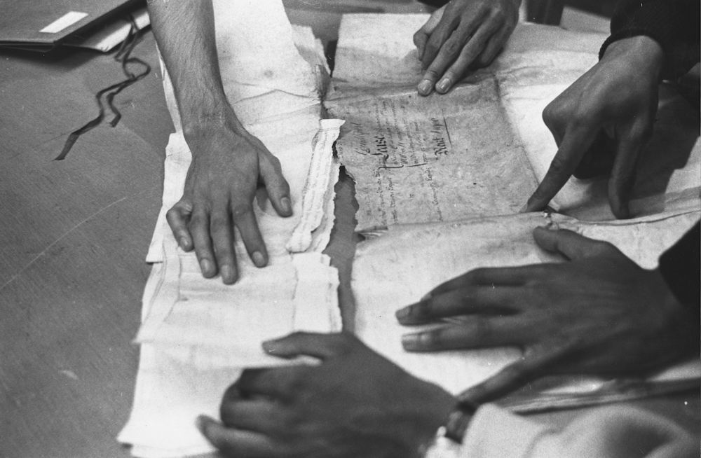 circa 1960: At the Schomburg Center for Research in Black Culture, in New York's public library, the hands of a group of scholars piece together a ship's document about a cargo of slaves brought to the United States. (Photo by Three Lions/Getty Images)