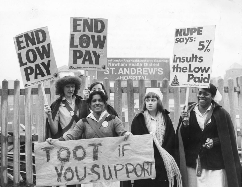 7th February 1979:  Nurses stand outside St Andrew's hospital in Bow, East London holding placards during a four hour strike. They are members of the 'NUPE' union which is defending their wages claim.  (Photo by Graham Turner/Keystone/Getty Images)
