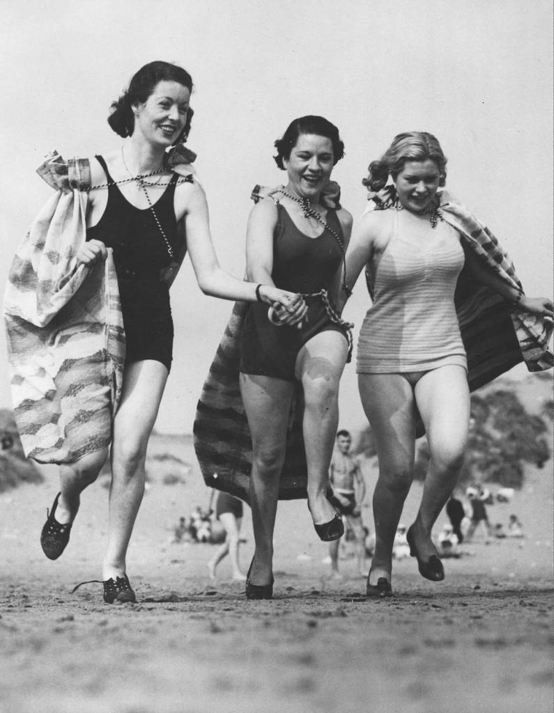 7th September 1937:  Three holidaymakers in high spirits on the beach at Porthcawl, South Wales.  (Photo by Richards/Fox Photos/Getty Images)
