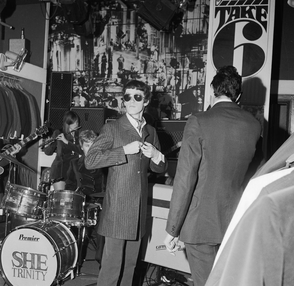 7th April 1967:  A customer at the Take 6 boutique in London's Wardour Street tries on a jacket as all-girl group She Trinity play live in the background. The boutique has been hiring bands to play during the lunch hour to attract more customers.  (Photo by Allan De Vries/BIPs/Getty Images)