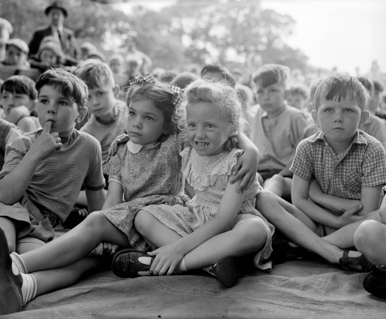 7th August 1954:  The faces on the  young audience show the differing opinions of the film they are watching at the open air cinema run by the LCC in Lewisham during school holidays.  (Photo by Meager/Fox Photos/Getty Images)