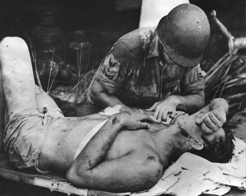 7th October 1942:  A Navy pharmacist's mate dressing the wounds of an injured survivor from USS 'Calhoun', sunk during an early assault on Guadalcanal,  the Solomon Islands.  (Photo by Keystone/Getty Images)