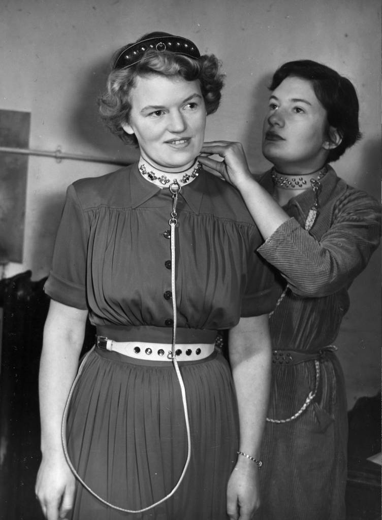 7th February 1951:  Valerie Davis of Chelsea, London, secures the dog collar around the neck of her friend Peggy Appleton, who wears two more canine contraptions; one as a headband and one around her waist, whilst the lead forms a long chatelaine from throat to waist, as on Valeries own accessories. Thanks to this new craze, pet shops are experiencing a run on these accessories.  (Photo by Fred Morley/Fox Photos/Getty Images)