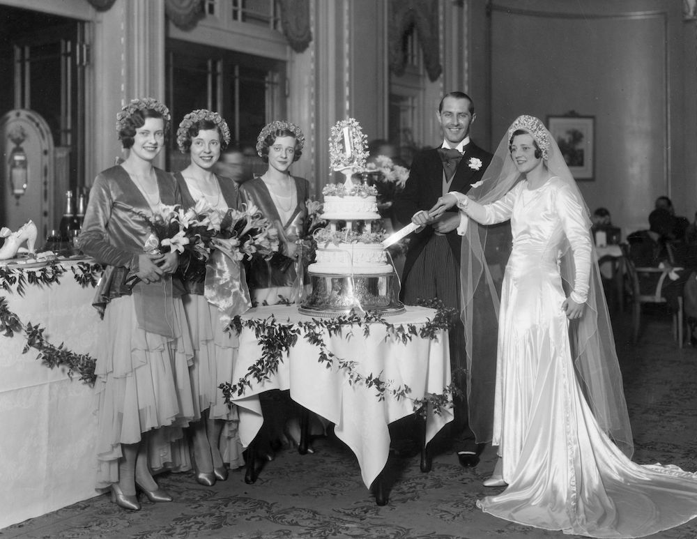 7th January 1930:  Dancer Audrey Tosh, of The Tosh Twins, and her husband George Thomas cutting their wedding cake beside their bridesmaids, sisters Iris, Esme and Natalie Tosh.  (Photo by Sasha/Getty Images)