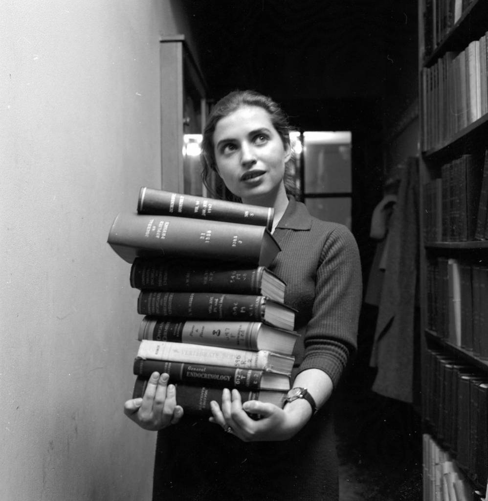 circa 1960: A student at Sarah Lawrence College in New York, with a pile of books. (Photo by Carsten/Three Lions/Getty Images)