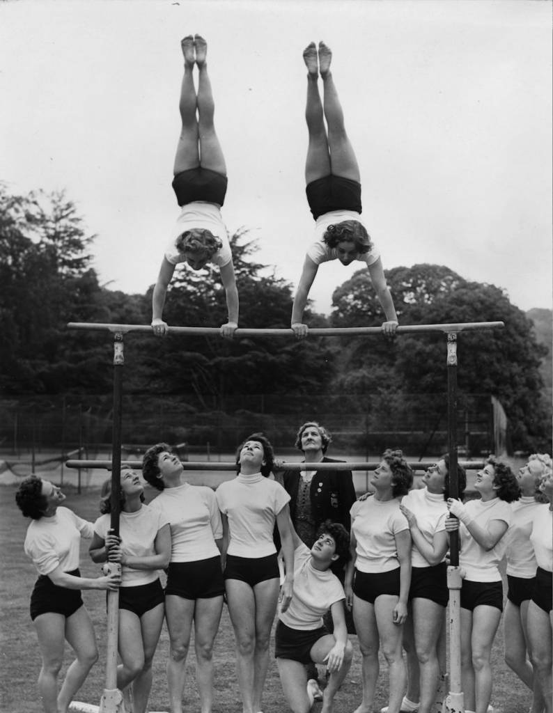 7th June 1952:  Margaret Thomas (left) and Gwynedd Lewis, two of the twelve finalists for the British Women's Olympic Gymnastic Team, perform a handstand on the asymmetric bars as the other ten watch them, during a training session at the National Physical Recreation Centre at Bisham Abbey, Buckinghamshire.  (Photo by G. R. Greated/Fox Photos/Getty Images)