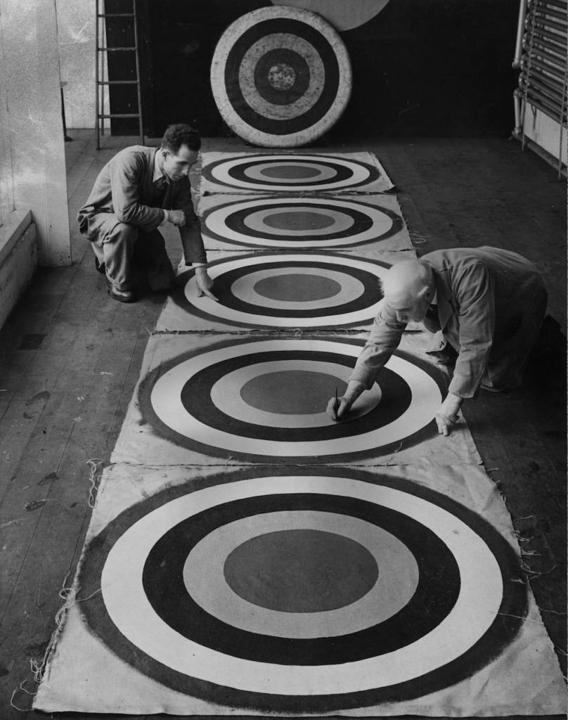 7th October 1935:  Bowmaker Mr W Law (right) and his son examine archery targets left out to dry in their workshop in Edinburgh.  (Photo by Fox Photos/Getty Images)