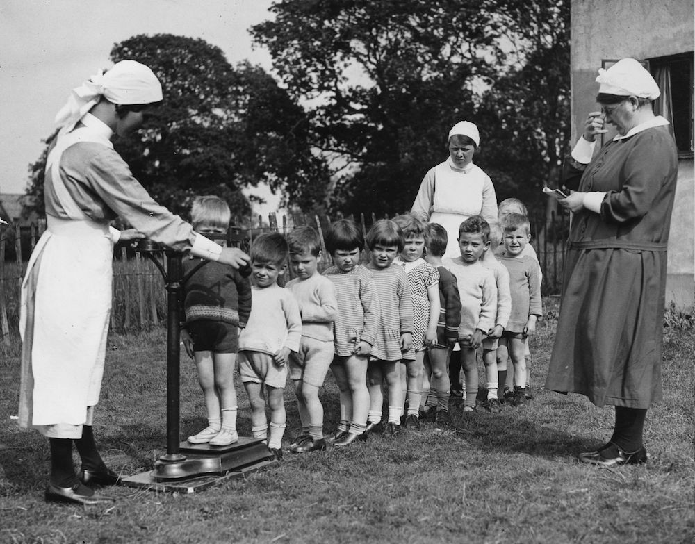 7th June 1934:  Children from the Arkley Toddlers Home, near High Barnet, England, lining up for the weekly weigh-in.  (Photo by Fox Photos/Getty Images)