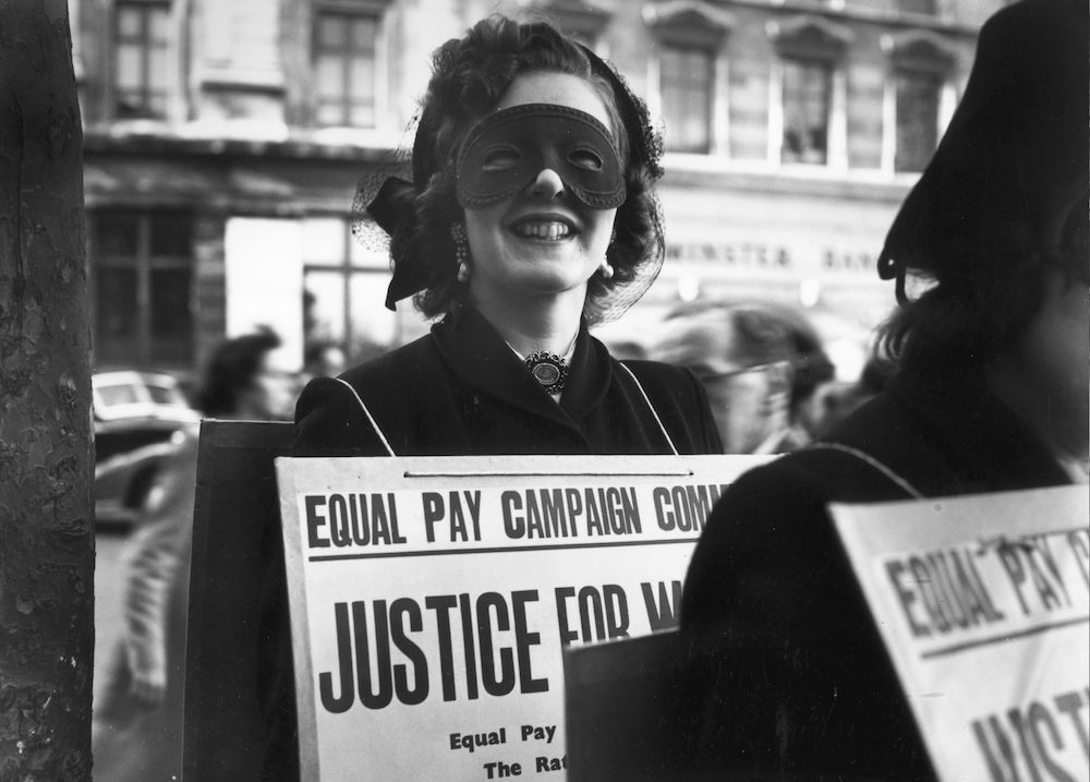 7th May 1952:  Sonia Banular wears a mask to a poster parade in London demanding equal pay for women.  (Photo by Keystone/Getty Images)