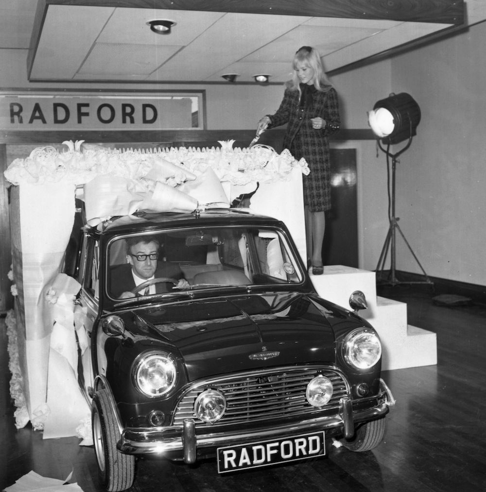7th October 1965:  Comedian Peter Sellers (1925-1980) drives a new luxury Radford Mini De Ville GT out of a giant wedding cake, as a gift for his new bride, actress Britt Ekland (above). This takes place in the Radford showrooms in King Street, Hammersmith, London.  (Photo by Wesley/Keystone/Getty Images)