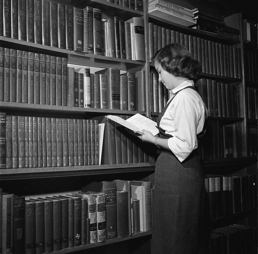 circa 1955: A student at the Wyoming Seminary, America leafs through a reference volume in the Bennet Library, part of the Sprague Memorial Building. (Photo by Al Barry/Three Lions/Getty Images)
