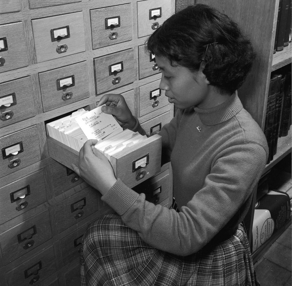 circa 1955: A Chinese student doing voluntary work abroad arranges library cards for the Chinese collection in a filing system at the Research Institute of Oriental Culture in Tokyo, Japan. The Institute is a branch of the Catholic University of Peking (Beijing). (Photo by Orlando /Three Lions/Getty Images)