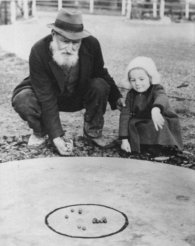 7th February 1938:  Both young and old are keen on the game of marbles at Tinsley Green in Sussex, where the World Marble Championship will be held, in front of the Greyhound Inn. Sam Spooner, 82, who won the championship more than 50 years ago, with Diana Winters aged two, who is already learning the game.  (Photo by Fred Morley/Fox Photos/Getty Images)