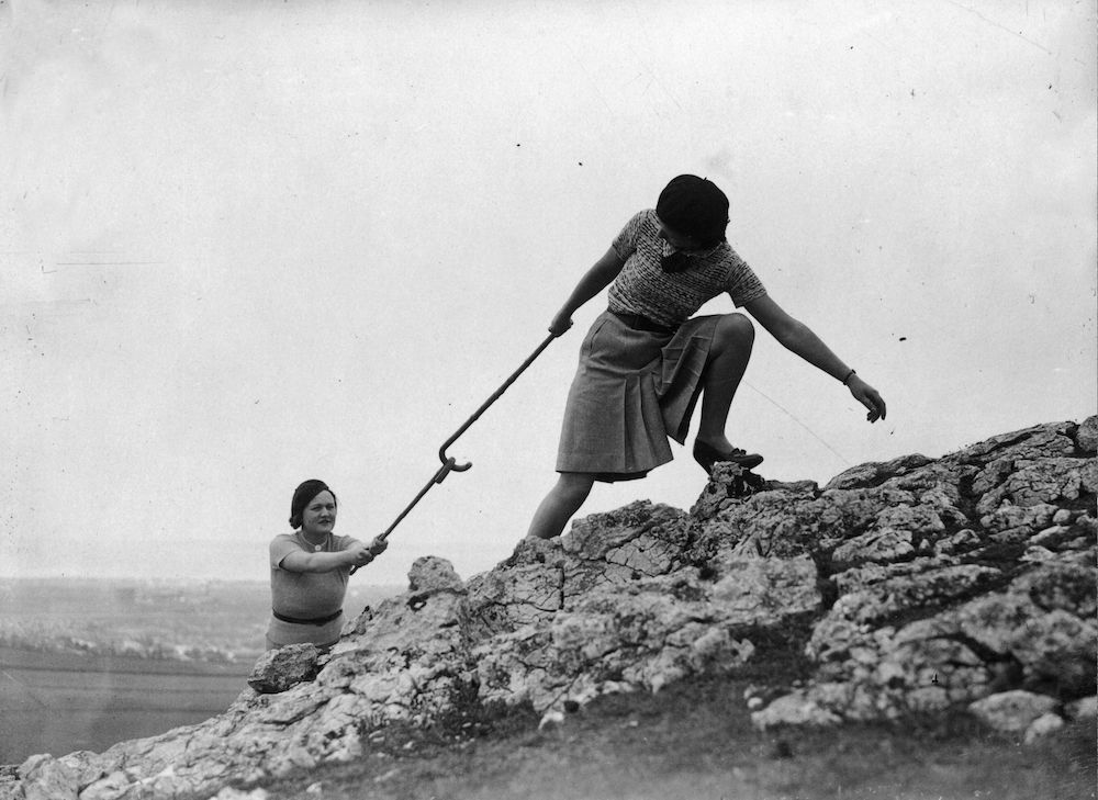 7th June 1935:  A woman giving her friend a pull-up using their walking sticks during a climb on the Great Orme at Llandudno, North Wales.  (Photo by E. Dean/Topical Press Agency/Getty Images)