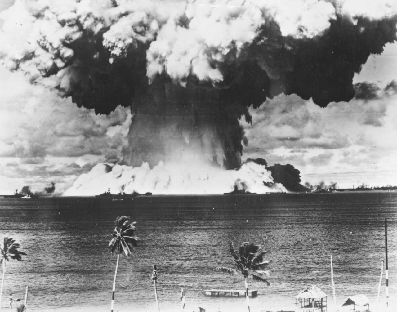 7th August 1946:  A mushroom cloud rises from the waters of Bikini Lagoon during the United States first series of underwater atomic tests. Ships of a 'Guinea Pig' fleet can be seen against the huge bank of water at the base of the explosion.  (Photo by Keystone/Getty Images)
