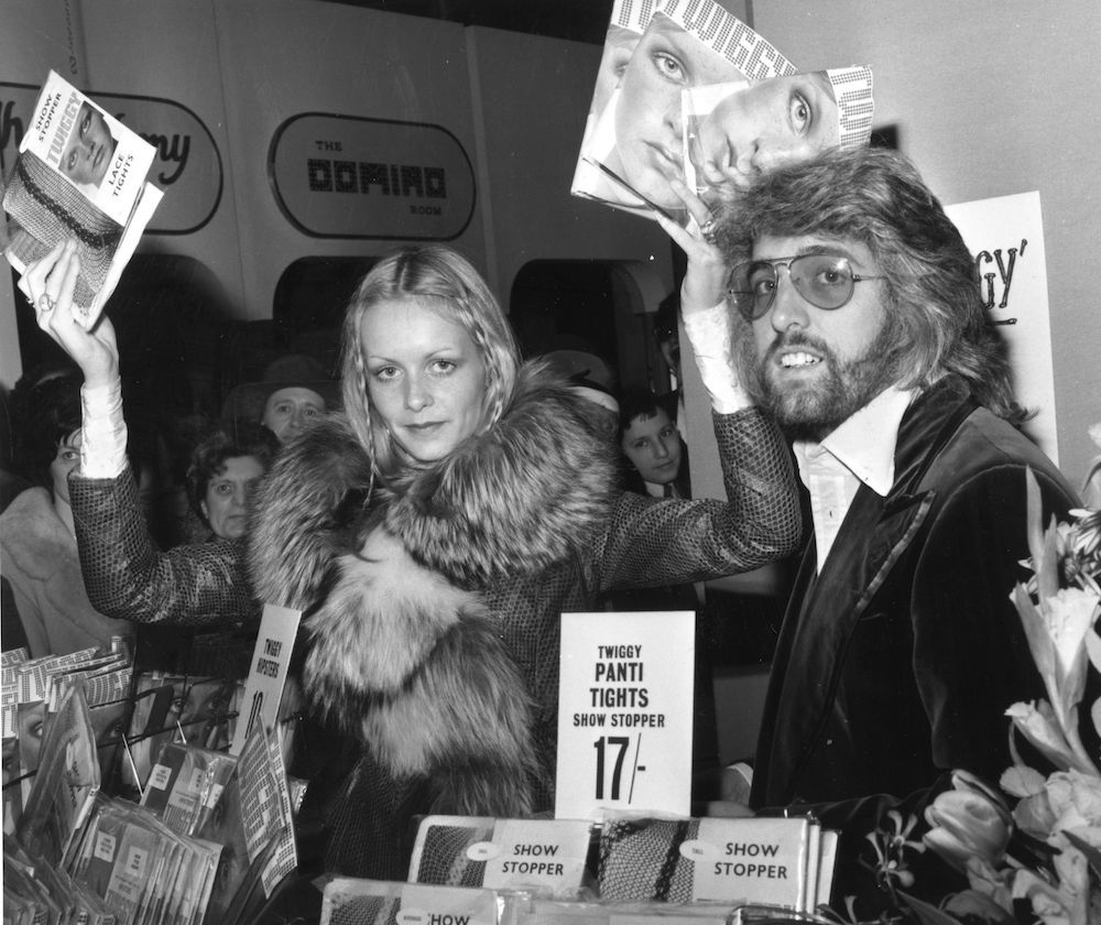 1st April 1970: British fashion model Twiggy (born Lesley Hornby) sells her own brand of tights in the hosiery department at Selfridges department store, London. Giving her a helping hand is her manager and boyfriend Justin de Villeneuve. (Photo by Evening Standard/Getty Images)