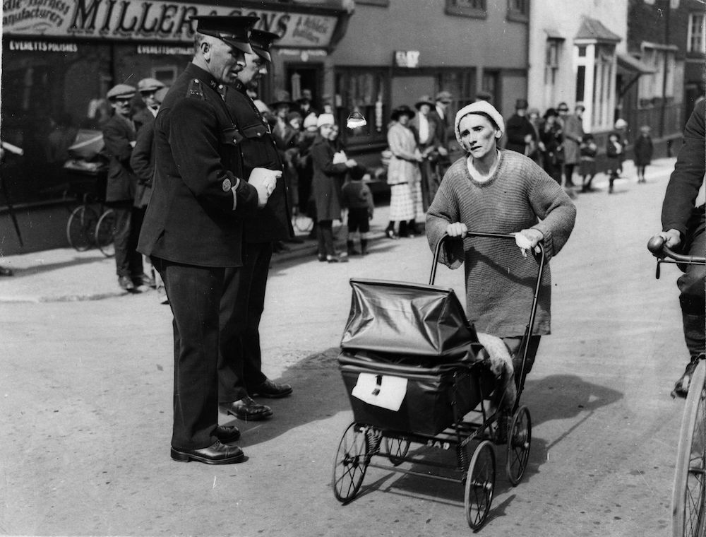 7th April 1923:  Mrs Edwards, one of the five contestants taking part in the London to Brighton Perambulator Walking Race, passing two policemen at Crawley.  (Photo by Topical Press Agency/Getty Images)