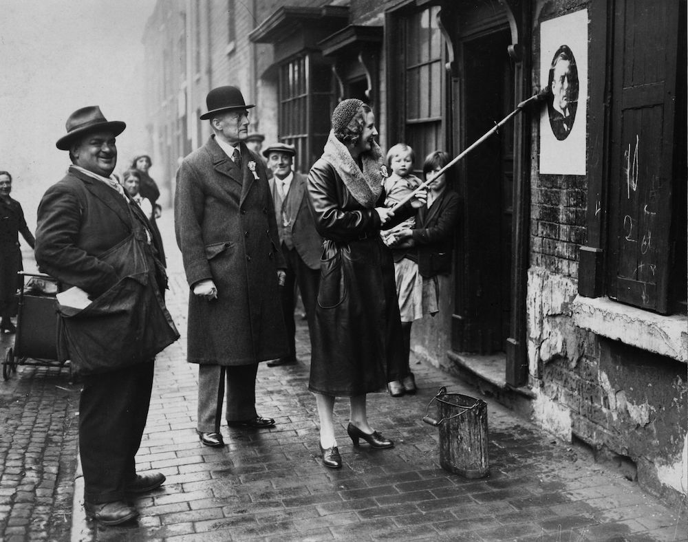 7th December 1931:  English politician Austen Chamberlain with his wife Lady Chamberlain who pauses during a tour of his constituency to put up a poster of her husband.  (Photo by Edward Gooch/Edward Gooch/Getty Images)