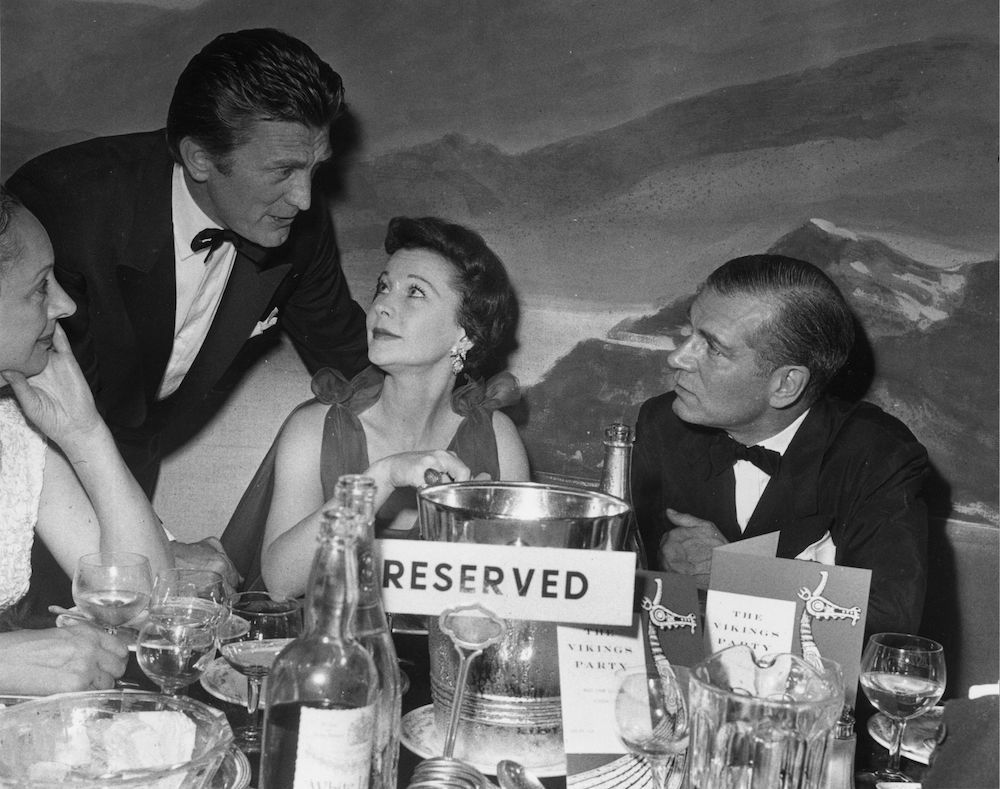 7th July 1958:  Actor Kirk Douglas talks to Lord and Lady Olivier, British actress Vivien Leigh (1913 - 1967), at the Mayfair Hotel.  (Photo by Evening Standard/Getty Images)