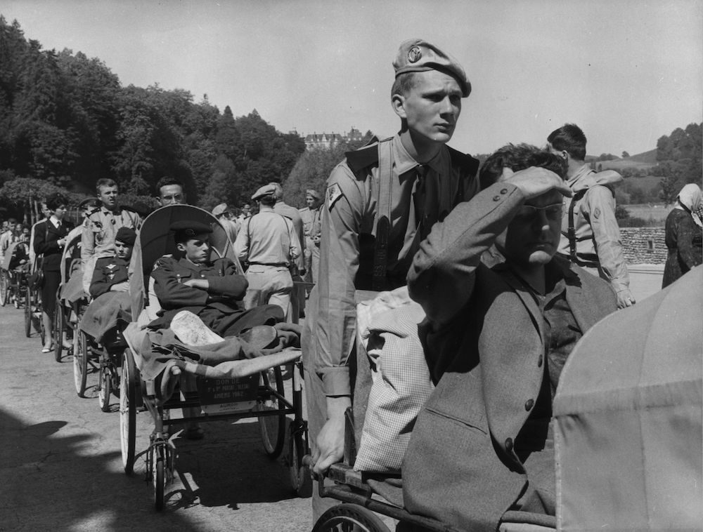 9th June 1964:  French soldiers helping transport some of the sick at Lourdes. 42,000 soldiers from 30 countries took part in the 7th annual International Military Pilgrimage, which went under the title of 'Friendship under Uniform above Frontiers'.  (Photo by Keystone/Getty Images)