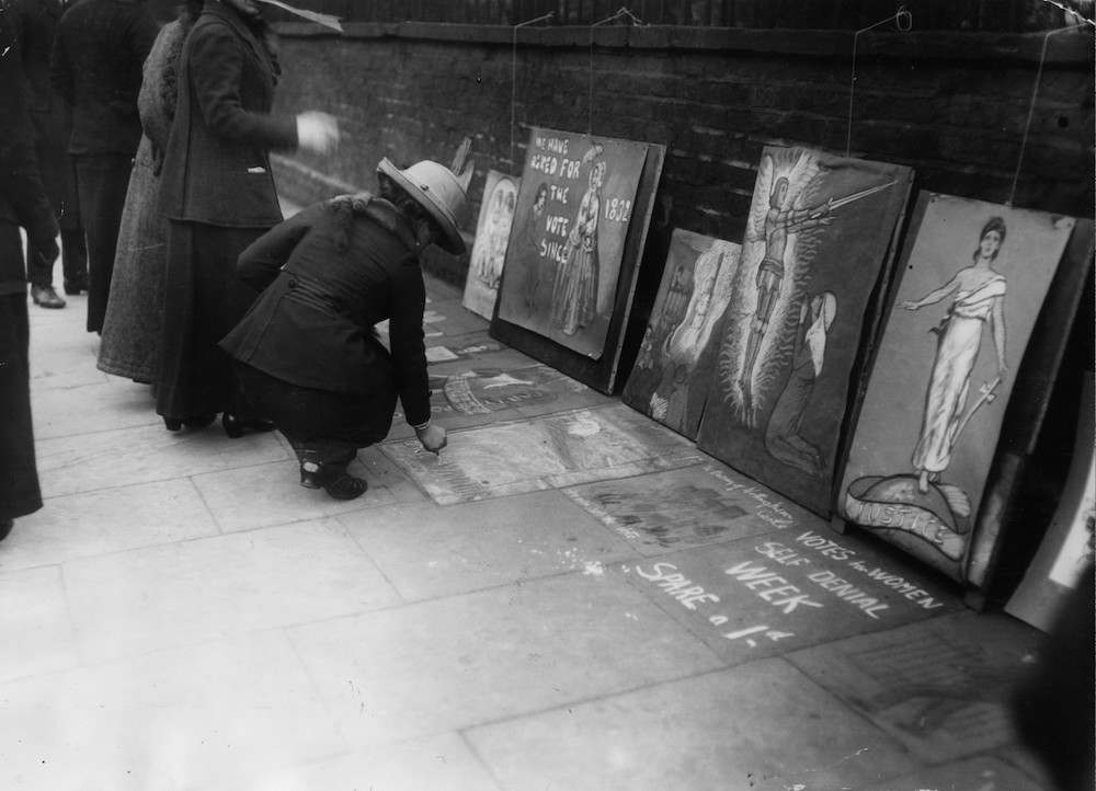 7th March 1913:  A suffragette adding to messages written by others on a pavement in Kensington.  (Photo by Topical Press Agency/Getty Images)