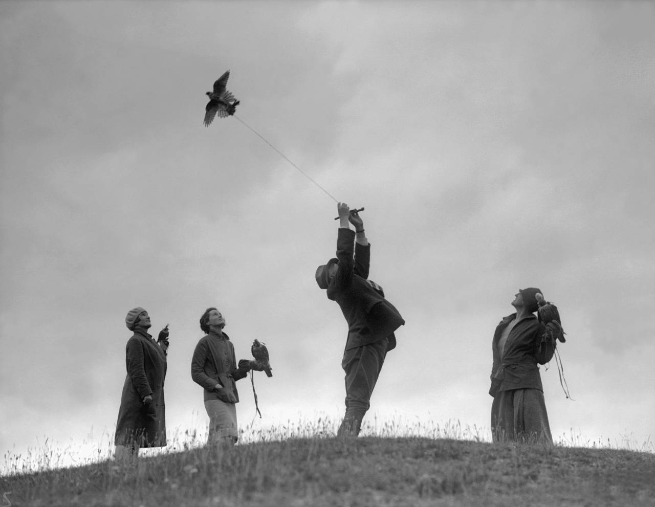7th August 1930:  Female members of the British Falcon and Hawk Club flying birds on the end of strings at Avebury in Wiltshire.  (Photo by Fox Photos/Getty Images)