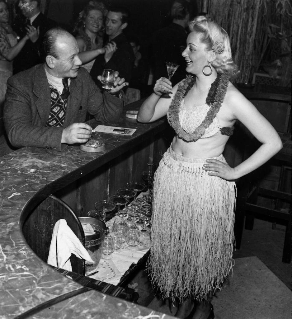 7th February 1950:  A hula hostess sharing a drink with a customer at a club in the Potsdamer Platz, Berlin.  (Photo by Keystone/Getty Images)