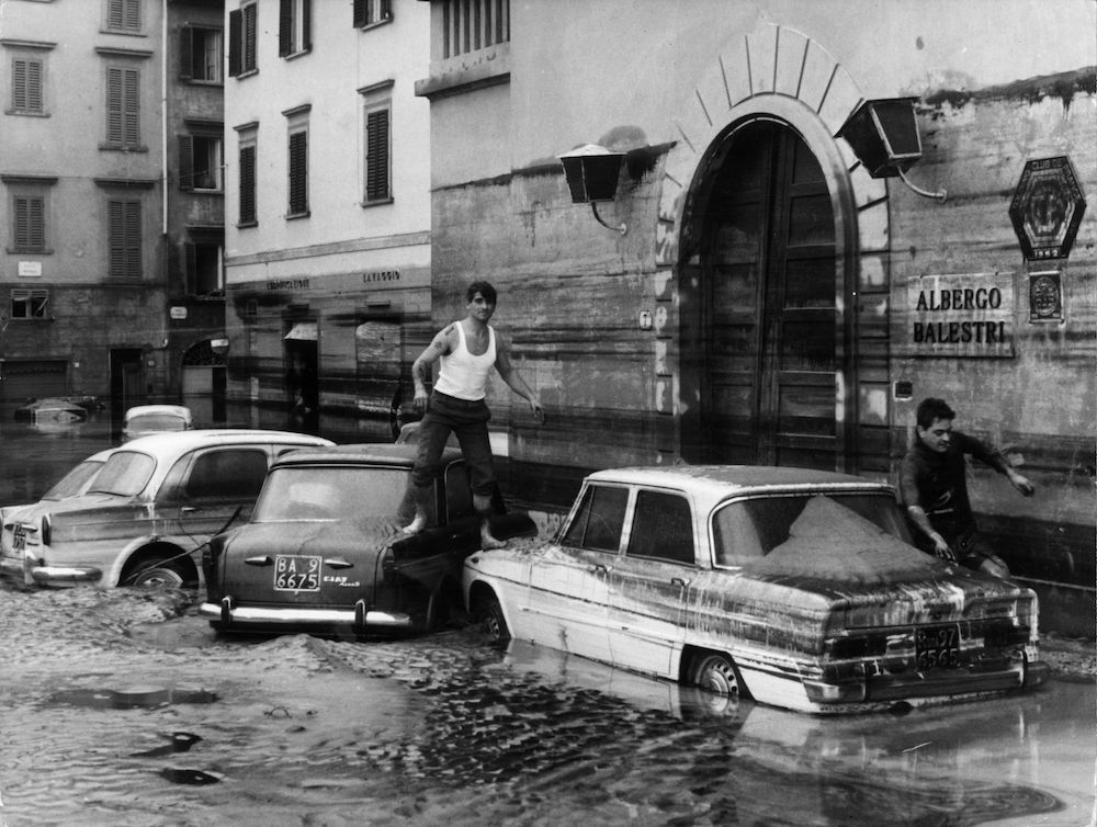 7th November 1966:  Pedestrians use marooned cars as stepping stones in the flooded streets of Florence after the River Arno had burst its banks.  (Photo by Keystone/Getty Images)