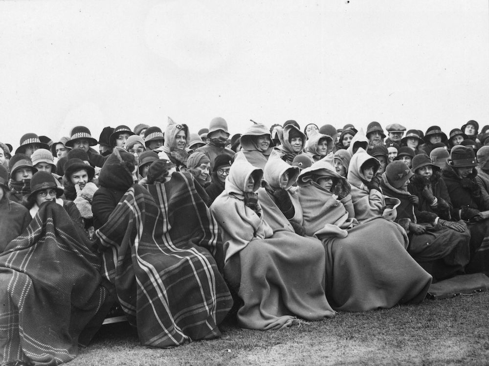 7th March 1931:  Spectators wrap up against the cold at an England V Scotland Women's Hockey International at Merton Abbey.  (Photo by A. Hudson/Topical Press Agency/Getty Images)