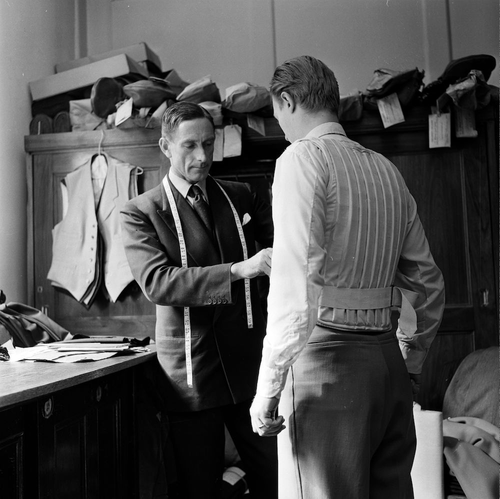 7th November 1956:  Leonard Barratt takes the measurements of a customer to be fitted with a bulletproof waistcoat in his second floor office of the Wilkenson's Sword Company in Pall Mall, London  (Photo by Harry Kerr/BIPs/Getty Images)