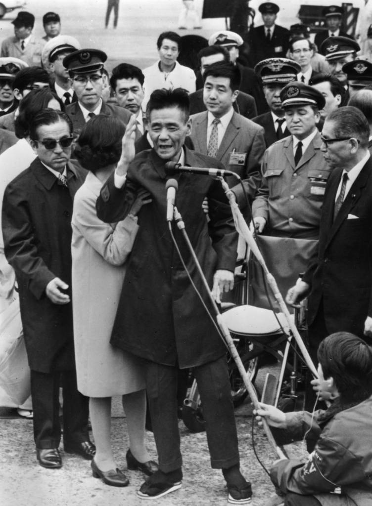 7th February 1972:  Shoichi Yokoi, a former sergeant in the Imperial Japanese Army, is helped to stand by a nurse as he acknowledges the cheers of the crowd at Tokyo airport. He has been in hiding in the jungle of Guam for 28 years, 31 years after he had left Japan to do his military service. In the welcoming party is the Japanese Health and Welfare Minister, Noboru Saito (on the right, wearing glasses).  (Photo by Keystone/Getty Images)