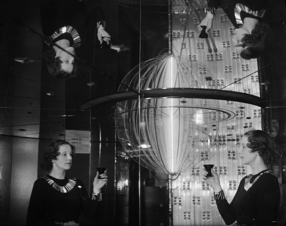 7th February 1938:  The Glass Train, sometimes called 'the travelling Crystal Palace' appears on display at London's Victoria Station for the first time. The train consists of a mobile exhibition of British glass, the outside being covered with mirrors and the inside furnished with glass. A woman is reflected four ways in the mirrored walls of the Rotunda.  (Photo by David Savill/Topical Press Agency/Getty Images)