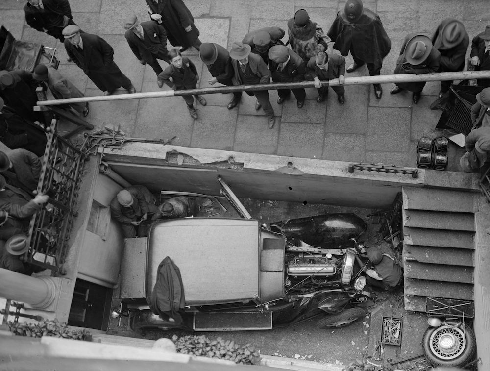 7th May 1930:  A car which has accidentally been driven into the cellar area in front of a basement flat.  (Photo by Fox Photos/Getty Images)