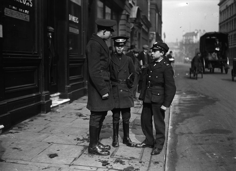 7th March 1930:  A group of uniformed young cable messengers talking in the street.  (Photo by Fox Photos/Getty Images)