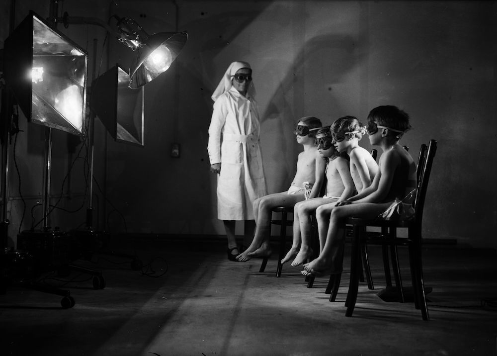 7th March 1930:  A group of children wearing goggles sit in front of large reflecting lamps at the Institute of Ray Therapy.  (Photo by Fox Photos/Getty Images)