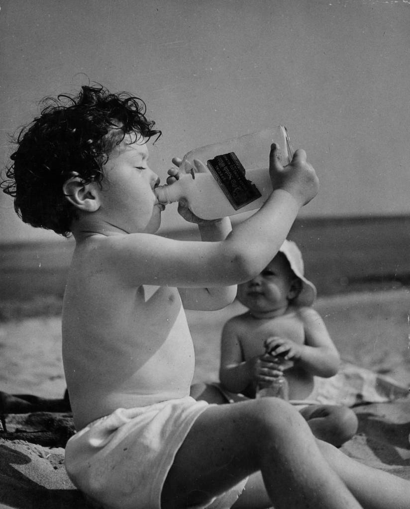7th July 1949:  James Shelley drinking milk from an old whisky bottle on Bantham Beach in Devon.  (Photo by George Konig/Keystone Features/Getty Images)