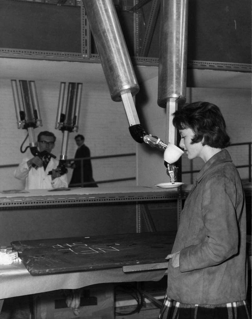 7th December 1960:  Carole North is fed a cup of tea by a Master Slave Manipulator at the Watford factory of Nuclear Equipment Ltd in Hertfordshire. The device, operated by Will Shepherd, is designed for the remote handling of equipment in the nuclear industry.  (Photo by Harry Todd/Fox Photos/Getty Images)