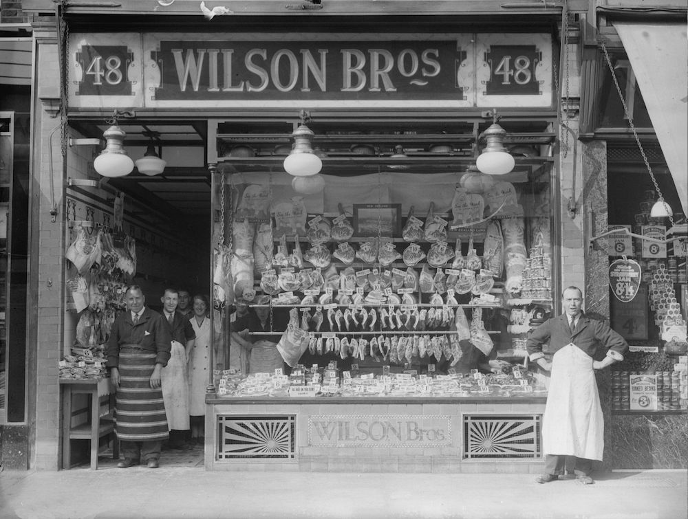 1937: The staff stand proudly by the window of a well stocked butcher's shop. (Photo by General Photographic Agency/Getty Images)