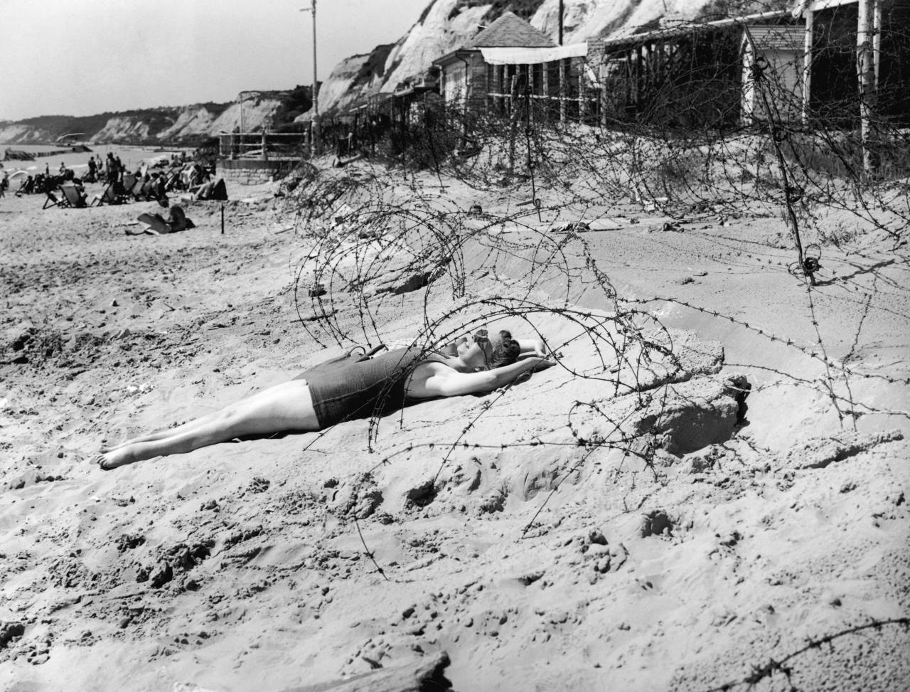 A woman sunbathes on a wartime bank holiday surrounded by barbed wire on the beach at Bournemouth, 7th August 1944.  (Photo by Topical Press Agency/Hulton Archive/Getty Images)