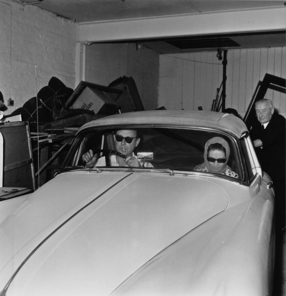 Society osteopath Stephen Ward (1912 - 1963) at the wheel of his Jaguar XK150 drophead coupe, as he and a female passenger leave his flat at Bryanston Mews, London, 7th June 1963. Ward first introduced Christine Keeler to British Secretary of State for War John Profumo. Their subsequent affair led to the Profumo scandal and the minister's resignation. (Photo by Cleland Rimmer/Evening Standard/Hulton Archive/Getty Images)